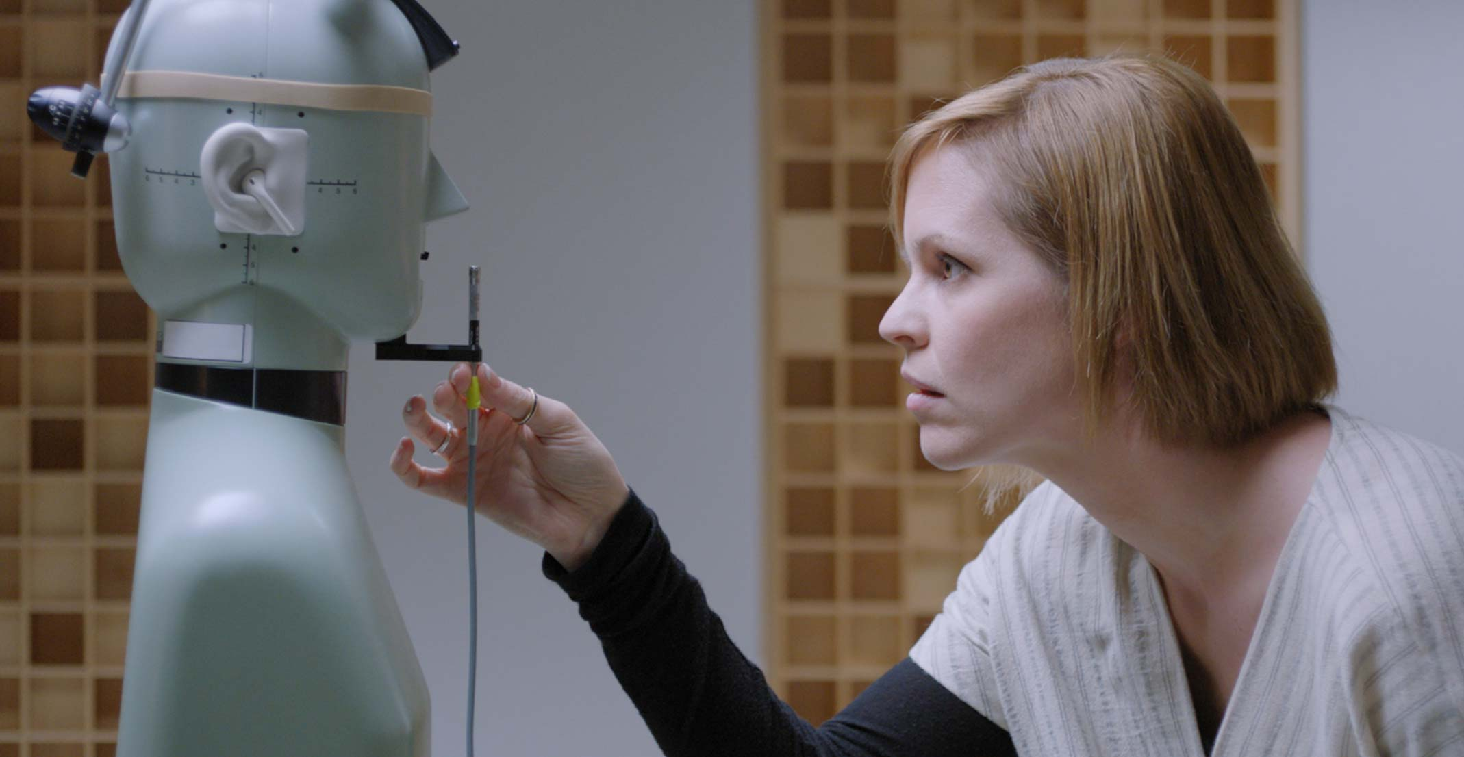 Suzie, a manager of an acoustic prototyping group at Apple, adjusts a microphone in front of a mannequin at an engineering lab in Cupertino.