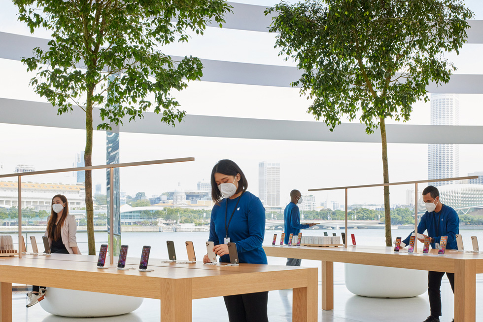 An Apple team member sets up an iPhone on display stands.