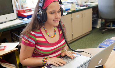 Student with headphones using a MacBook Pro.