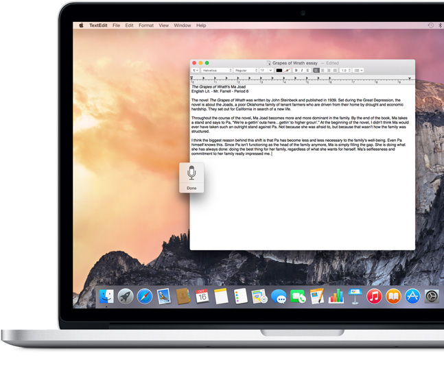 MacBook Pro showing a Pages document with the dictation icon and an essay being dictated about The Grapes of Wrath.