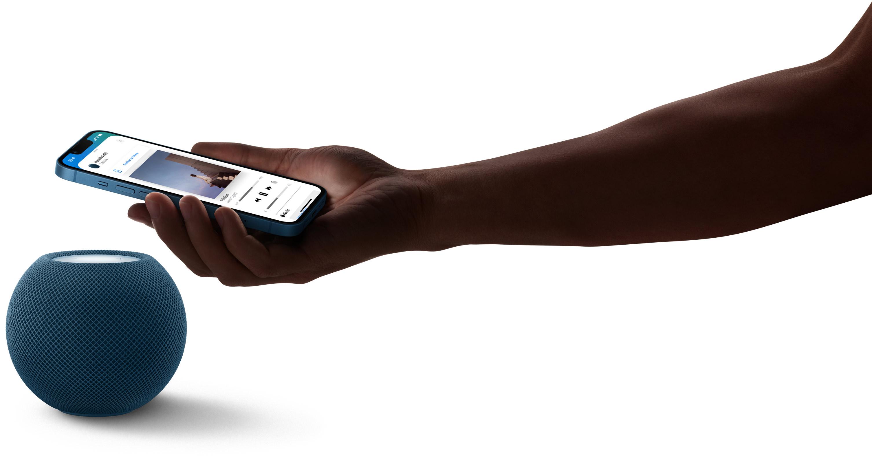 HomePod mini blanc au-dessus duquel la main d'une personne tient un iPhone. L'écran de cet iPhone montre de la musique en cours d'écoute.