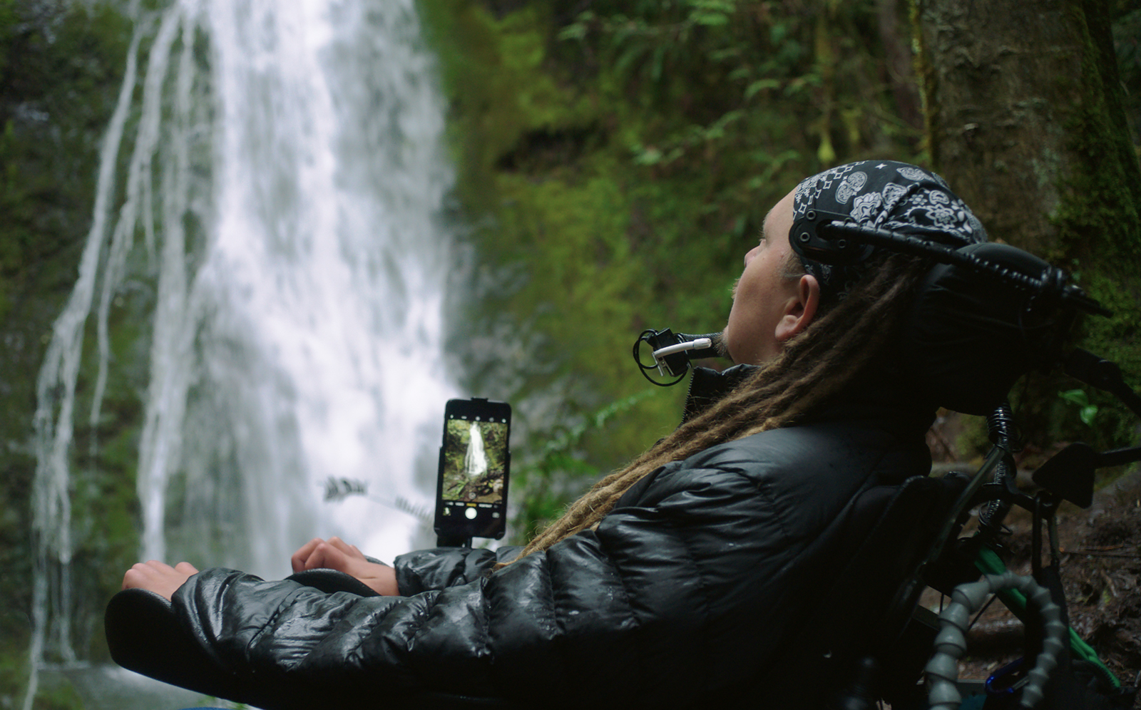 In front of a waterfall, a man in a wheelchair uses Switch Control assistive technology to operate his iPhone camera