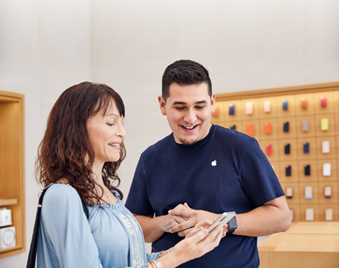 An Apple retail employee demonstrates an iPhone to a customer