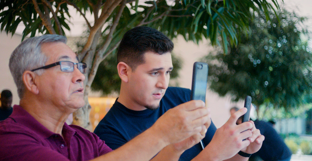 Jeronimo, a Technical Specialist, shows an Apple Store customer how to use the camera on iPhone.