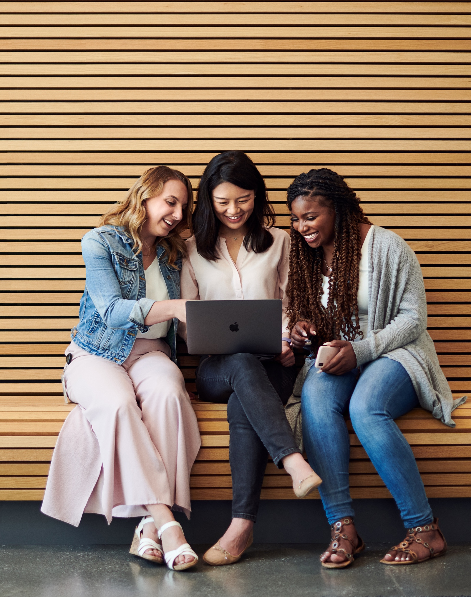 Three female Apple employees sit together on a bench while looking at a MacBook.