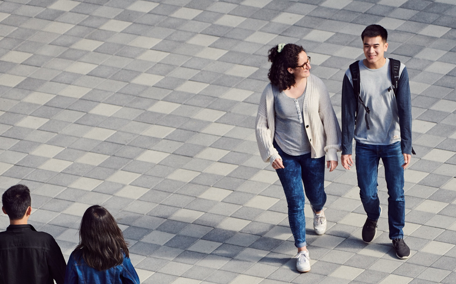 Apple employees walk across a courtyard on an Apple campus while talking.