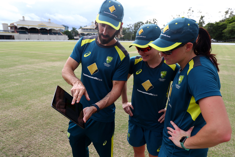 Australia Women's Cricket Team player and coach reviewing performance stats on iPad.