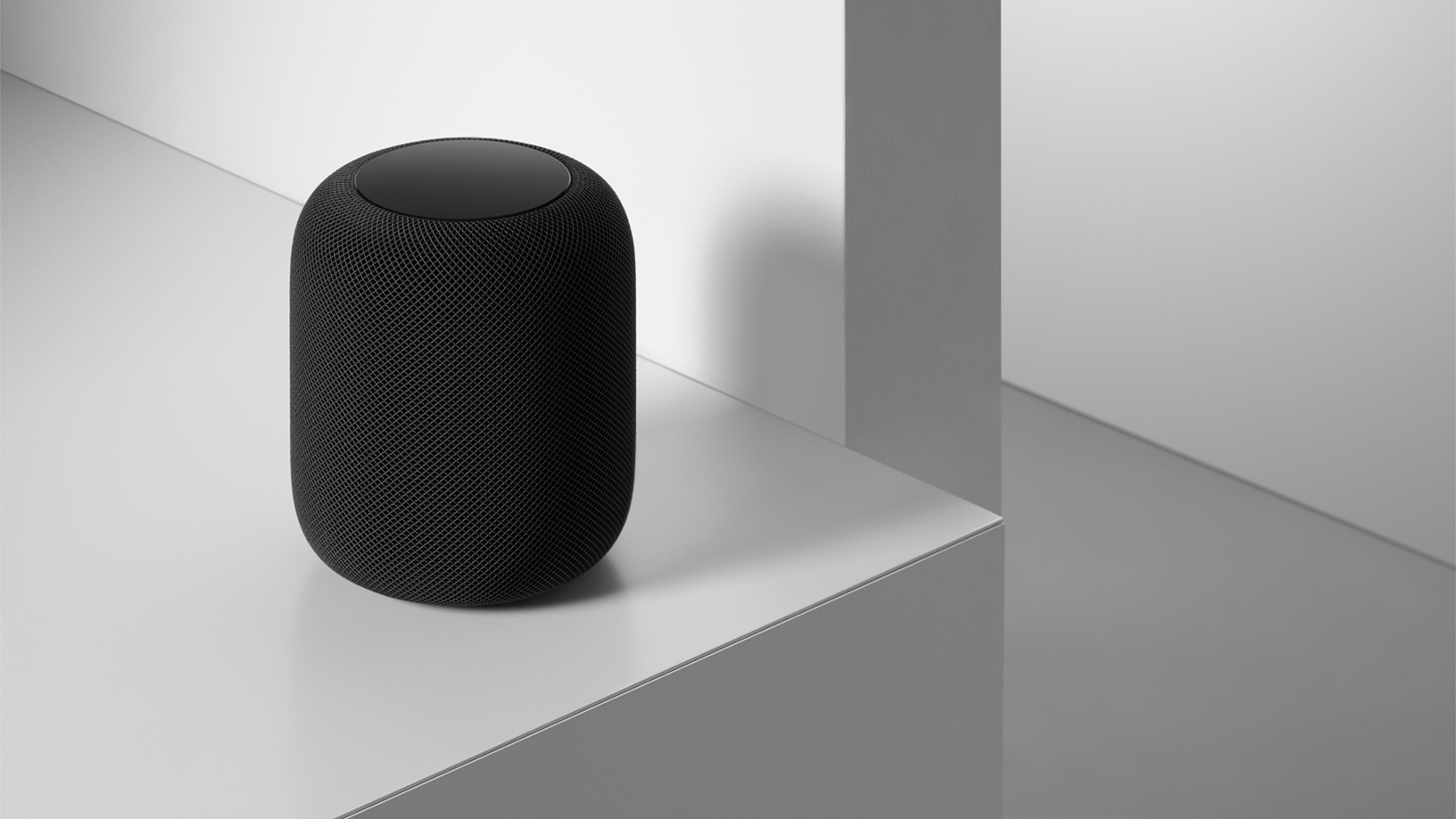 A space grey HomePod on a table.