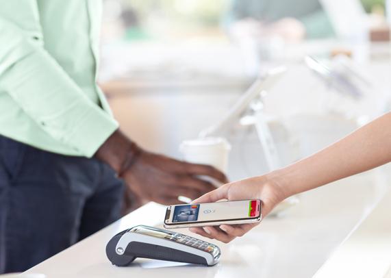 Nutzung von Apple Pay an einem Terminal zum kontaktlosen Bezahlen.