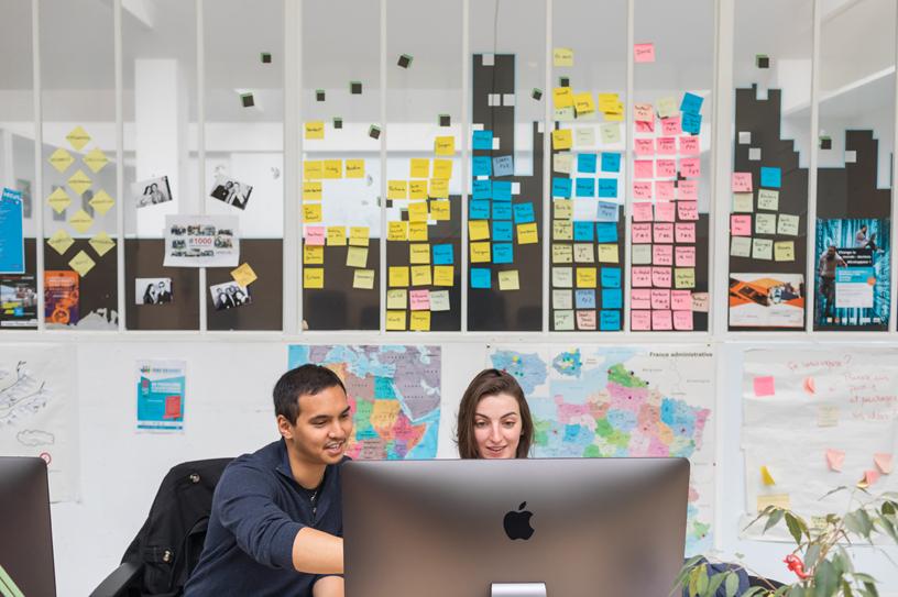 Deux personnes travaillant sur un iMac.
