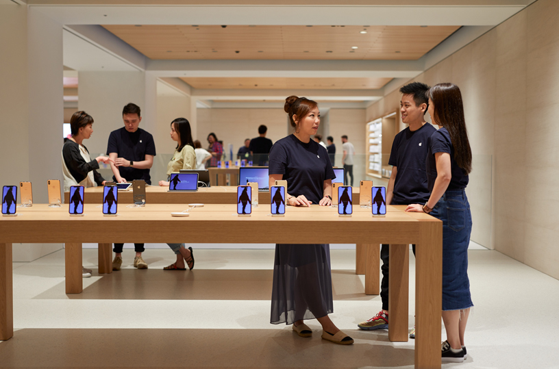 Apple employees standing next to iPhone displays at Apple Marunouchi.