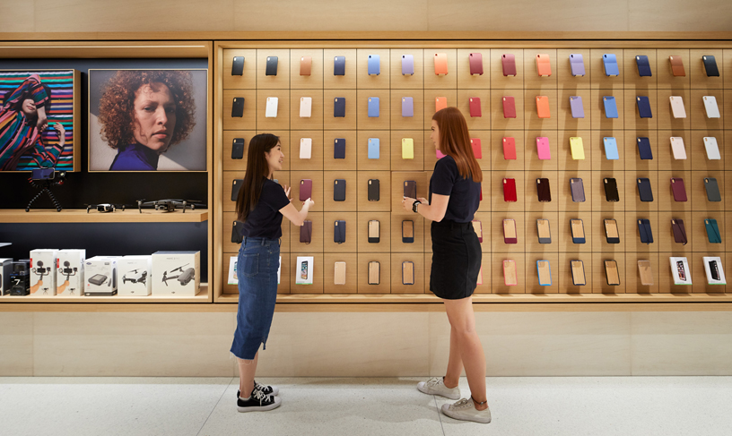 People standing in front of many iPhone cases displayed on wall.