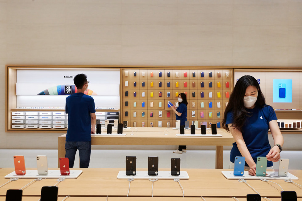 Retail team members setting up iPhone devices on display tables inside Apple Changsha.