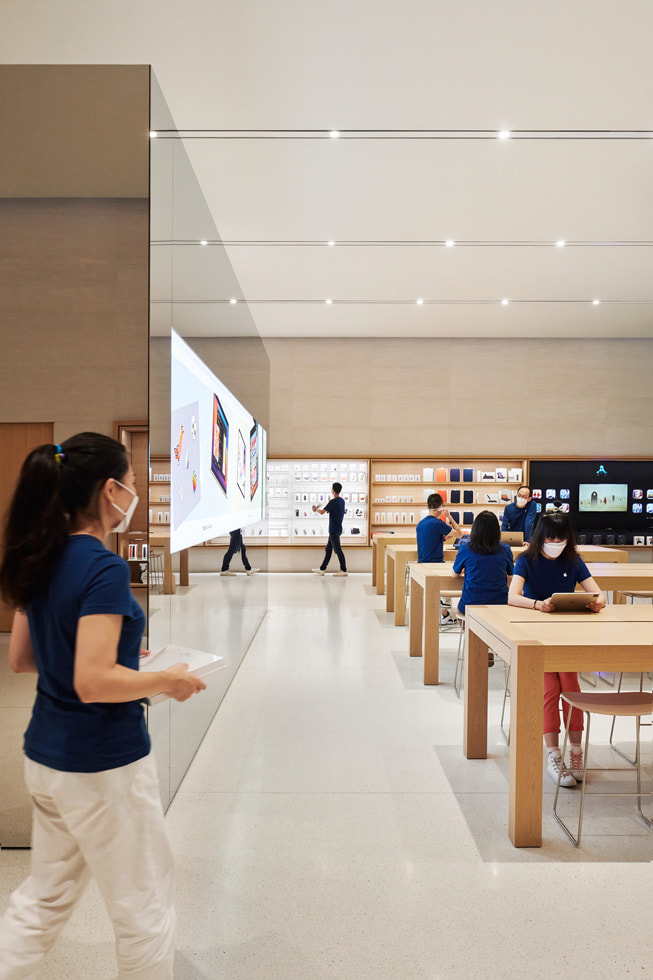 A number of display tables with retail team members and a freestanding video wall inside Apple Changsha.