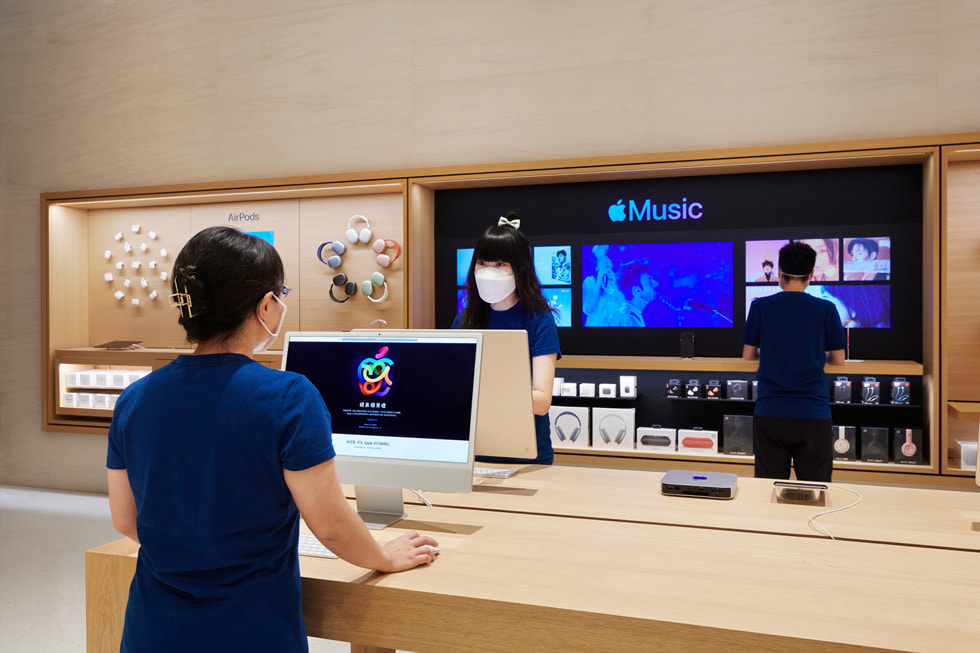 Retail team members on display tables using iMac inside Apple Changsha.
