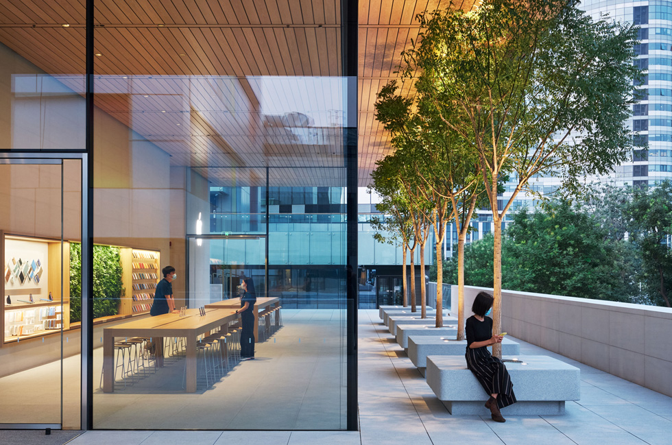 A glass corner of the Apple Sanlitun and an outdoor tree-lined seating area show how seamlessly the store's design transitions from indoor to outdoor.