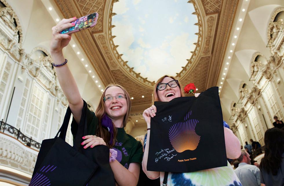 Des clientes prennent un selfie avec leurs achats Apple sous la coupole d'Apple Tower Theatre et sa voûte céleste peinte.