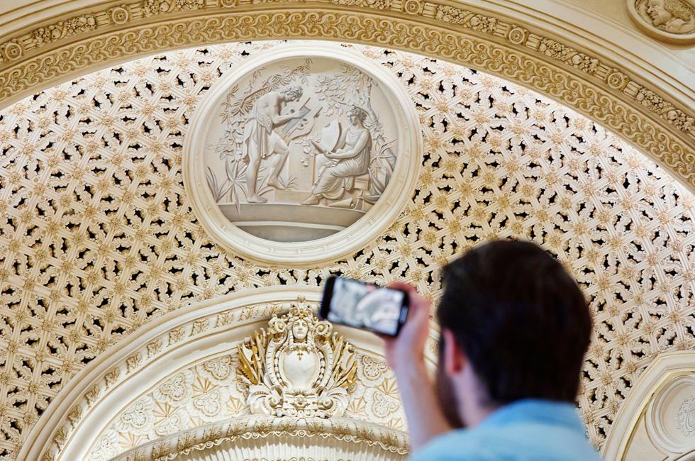 Un client prend une photo des détails du décor d'Apple Tower Theatre avec son iPhone.