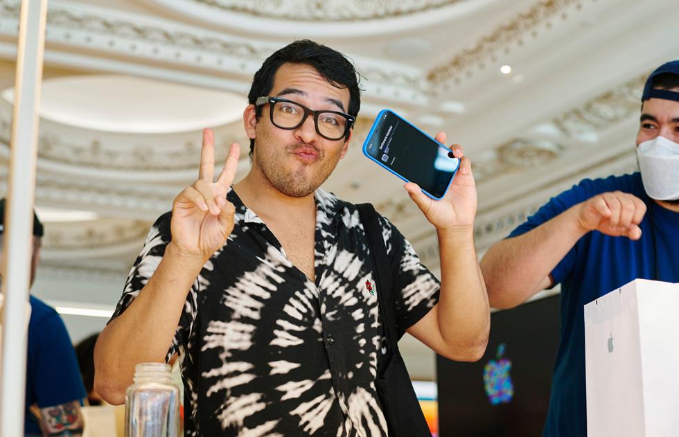 Un client fait un signe de victoire d'une main et tient son iPhone12 dans l'autre à Apple Tower Theatre.