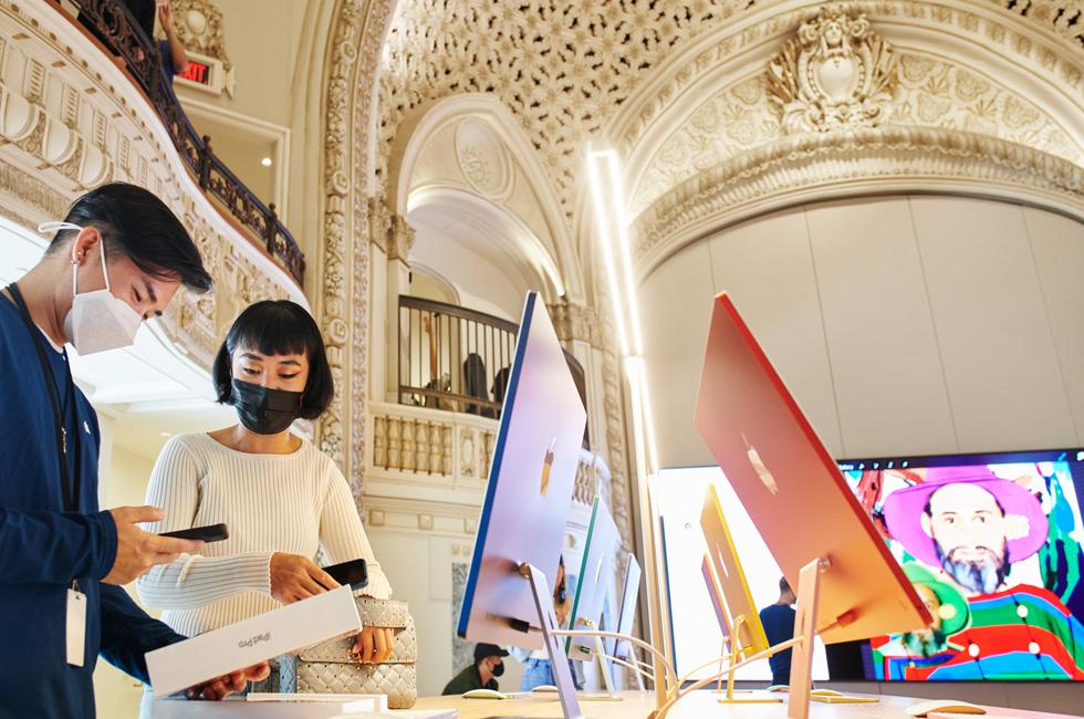Un membre de l'équipe Apple accompagne une cliente qui achète un nouvel iPadPro à Apple Tower Theatre.