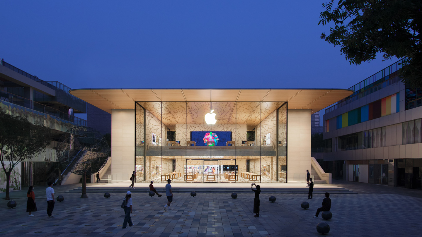 An exterior view of the Apple Sanlitun storefront at dusk shows a lighted store interior that emphasizes the transparency and flow of the building's design.