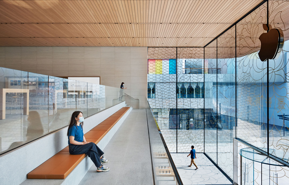 An Apple employee, wearing a face mask and seated on a bench in the upper-level Viewing Gallery, looks out onto the square.