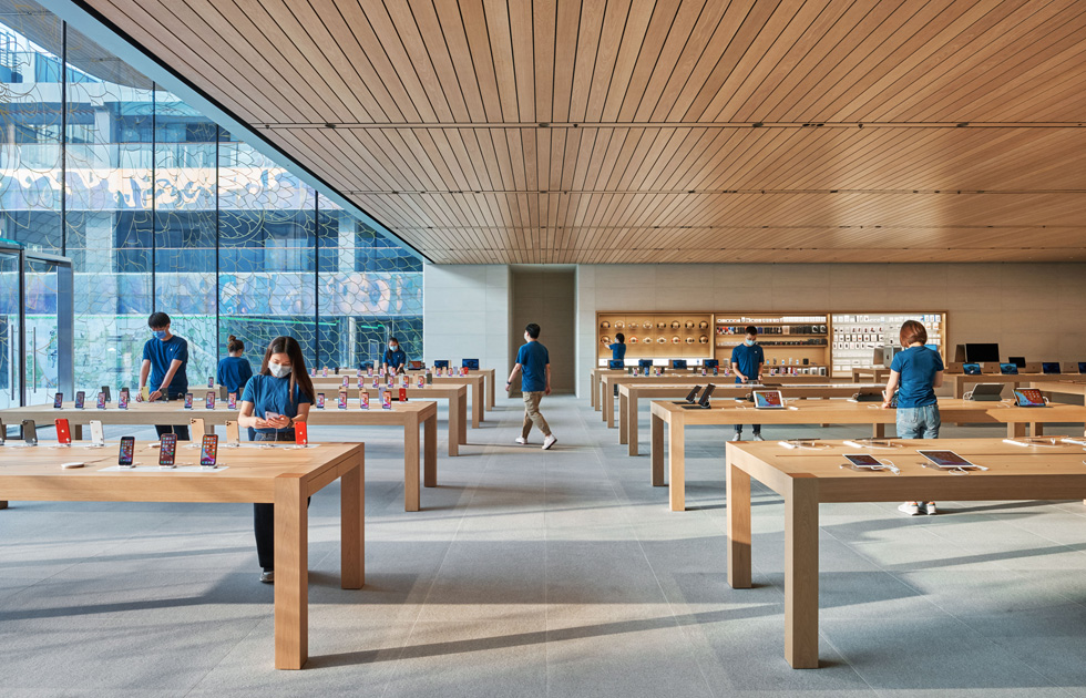 Apple employees at product display stations.