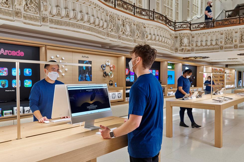 Des membres de l'équipe de l'Apple Tower Theatre devant les présentoirs iMac et iPad.
