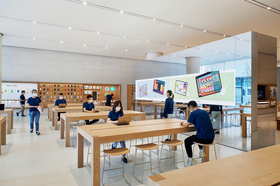 A number of display tables with customers and a freestanding video wall inside Apple Changsha.