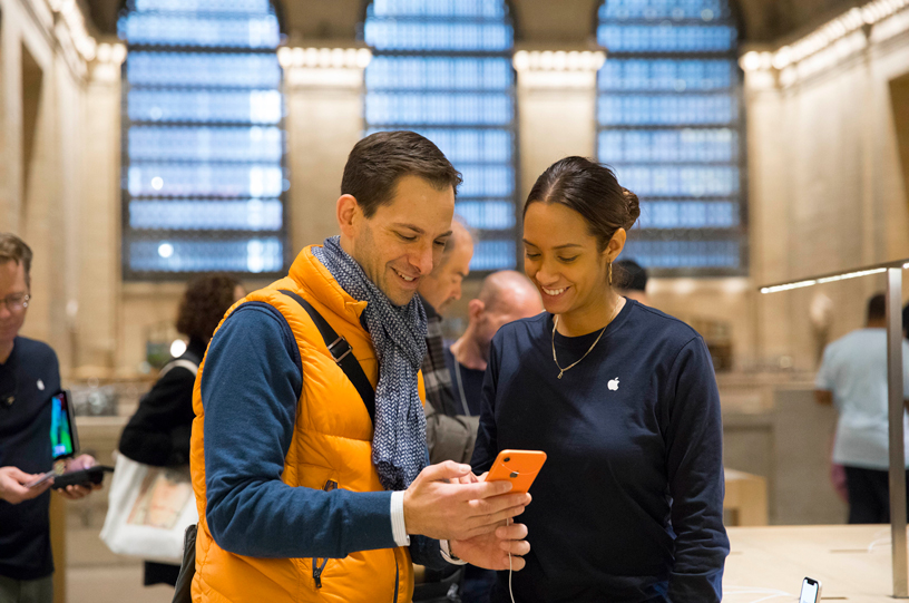 An Apple Grand Central team member assisting a customer with the iPhone XR.