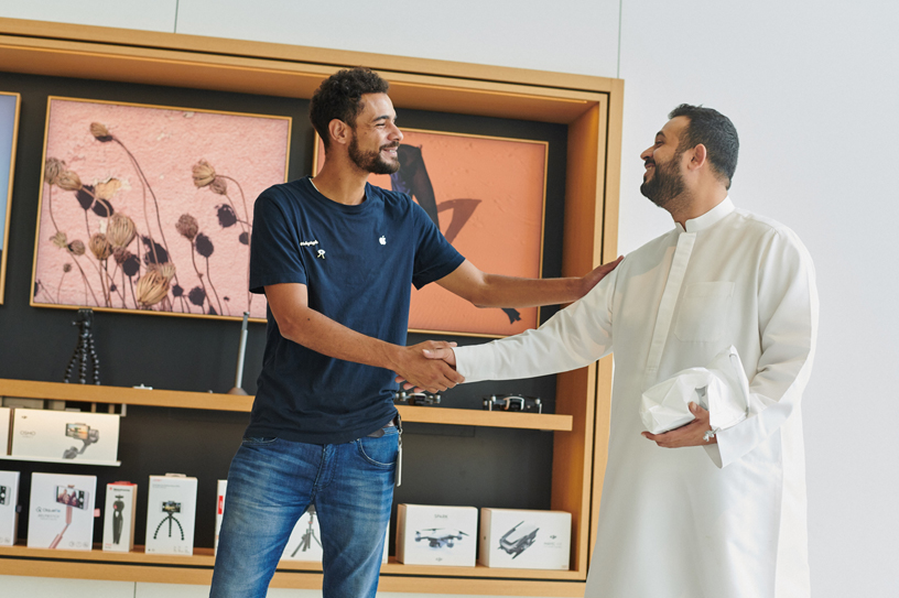 An Apple team member shaking hands with a customer.