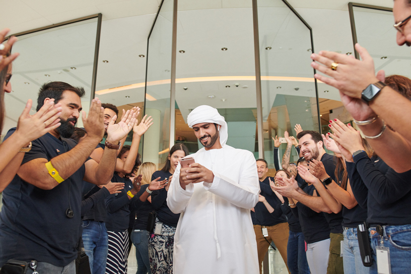 Customer surrounded by clapping Apple team members.