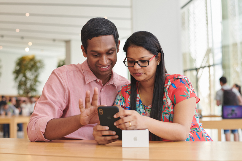 Male and female customer try out the iPhone Xs Max.