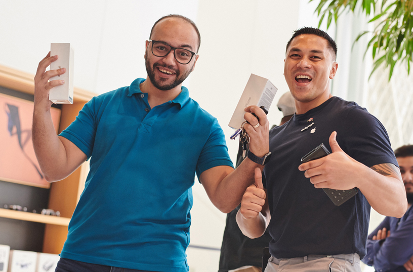 Customer holding up two iPhone Xs boxes with an Apple team member.