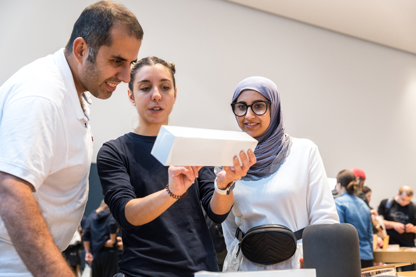 An Apple team member shows two customers details on an Apple Watch Series 4 box.
