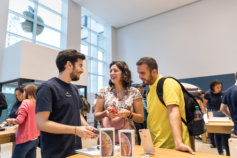 An Apple team member talks with two customers checking out iPhone Xs Max.