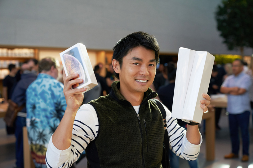 A man holds up boxes for the iPhone Xs and Apple Watch Series 4.