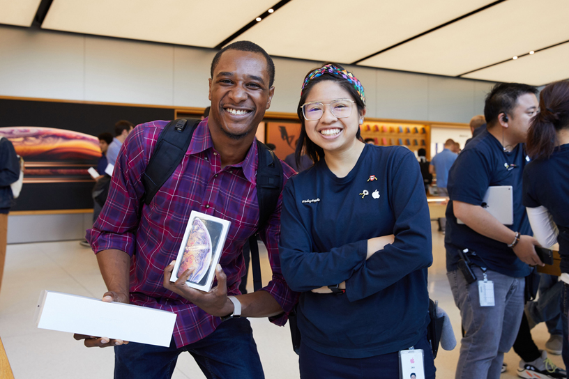 A customer holding boxes for the Apple Watch Series 4 and iPhone Xs poses for a photo with an Apple team member.