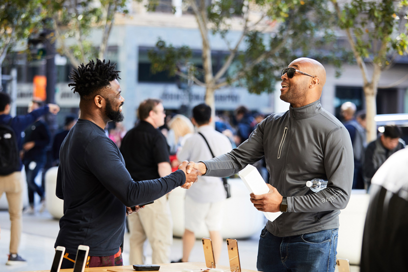 An Apple team member shakes hands with a customer.