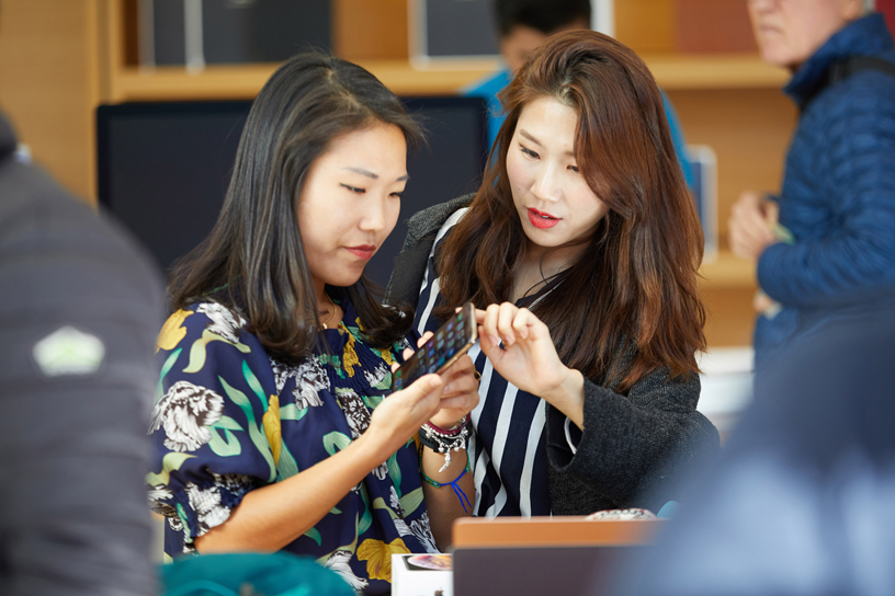 Two women examine the iPhone Xs.