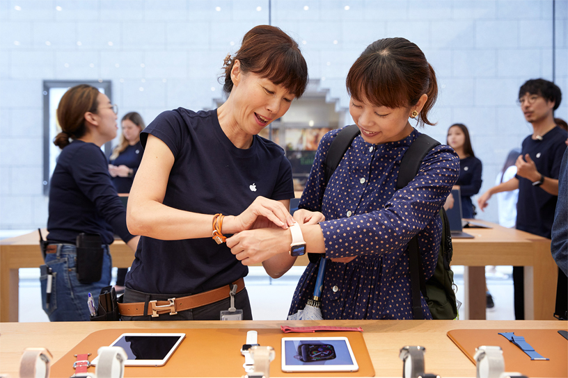 An Apple Kyoto team member helping a young woman try on the Apple Watch Series 4.
