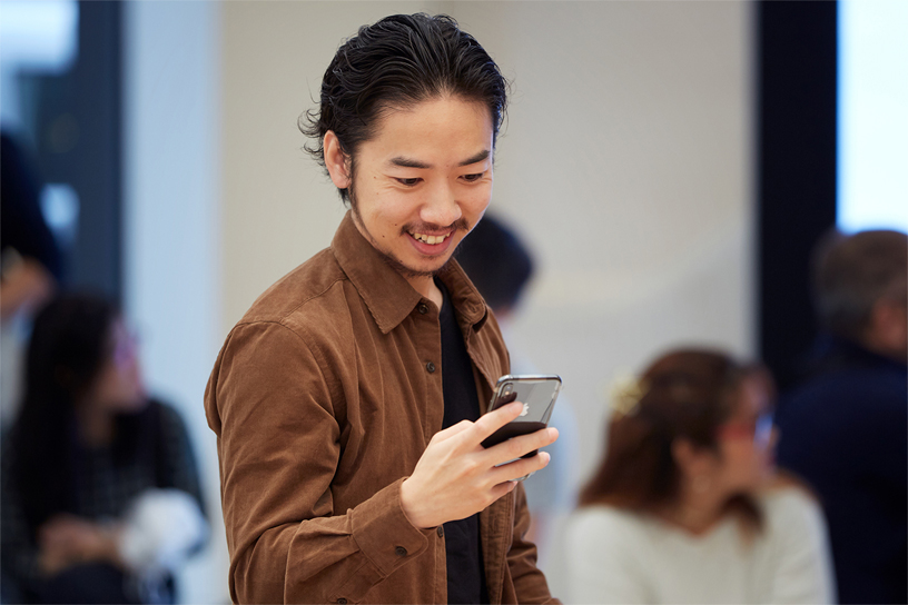 A young man interacting with the new iPhone Xs.