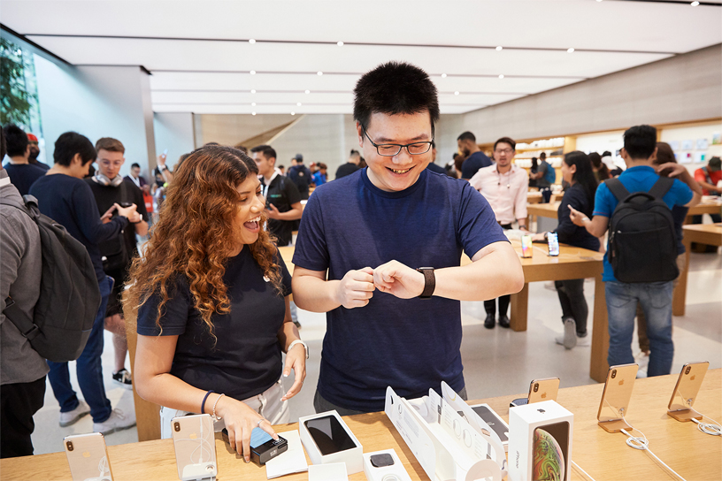 An Apple team member assisting a customer wearing the Apple Watch Series 4.
