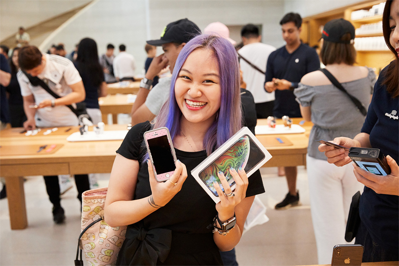 A young woman trading in an old iPhone for the new iPhone Xs Max.