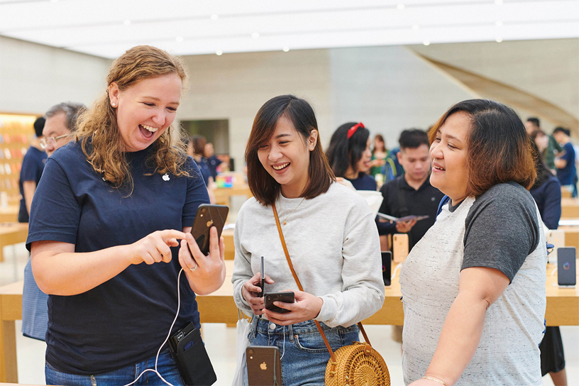 Apple team member shows iPhone XR to two customers.