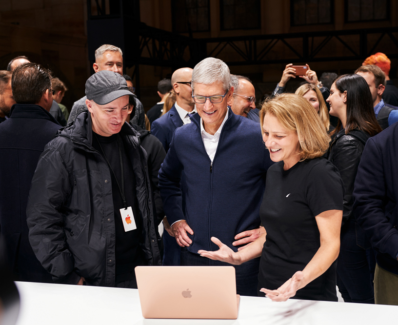 KAWS and Tim Cook check out the MacBook Air with an Apple team member.