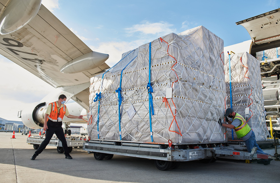 UPS Worldport employees transport palettes of iPhone 12, iPhone 12 Pro, and iPad Air shipments from an airplane.