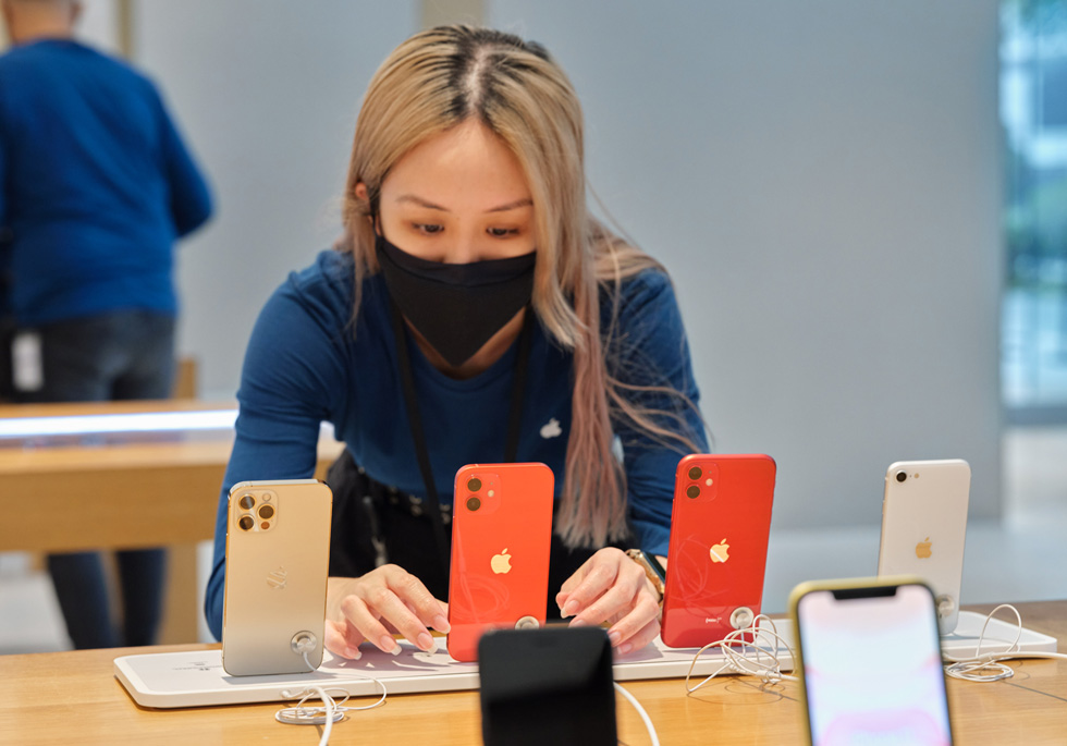 An Apple Orchard Road team member adjusts a display of iPhone SE, iPhone 11, iPhone 12, and iPhone 12 Pro.