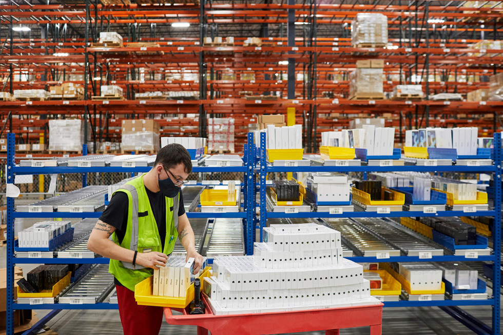 A distribution center employee preparing Apple product for shipment.