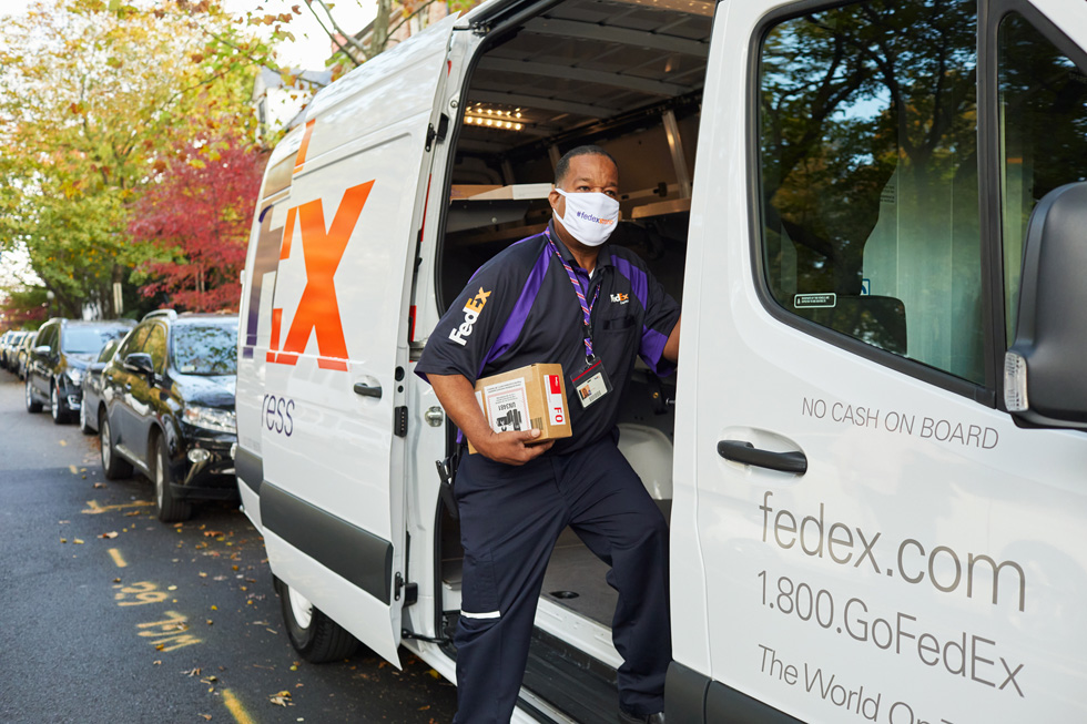 A FedEx worker delivers an Apple package from a FedEx delivery van.